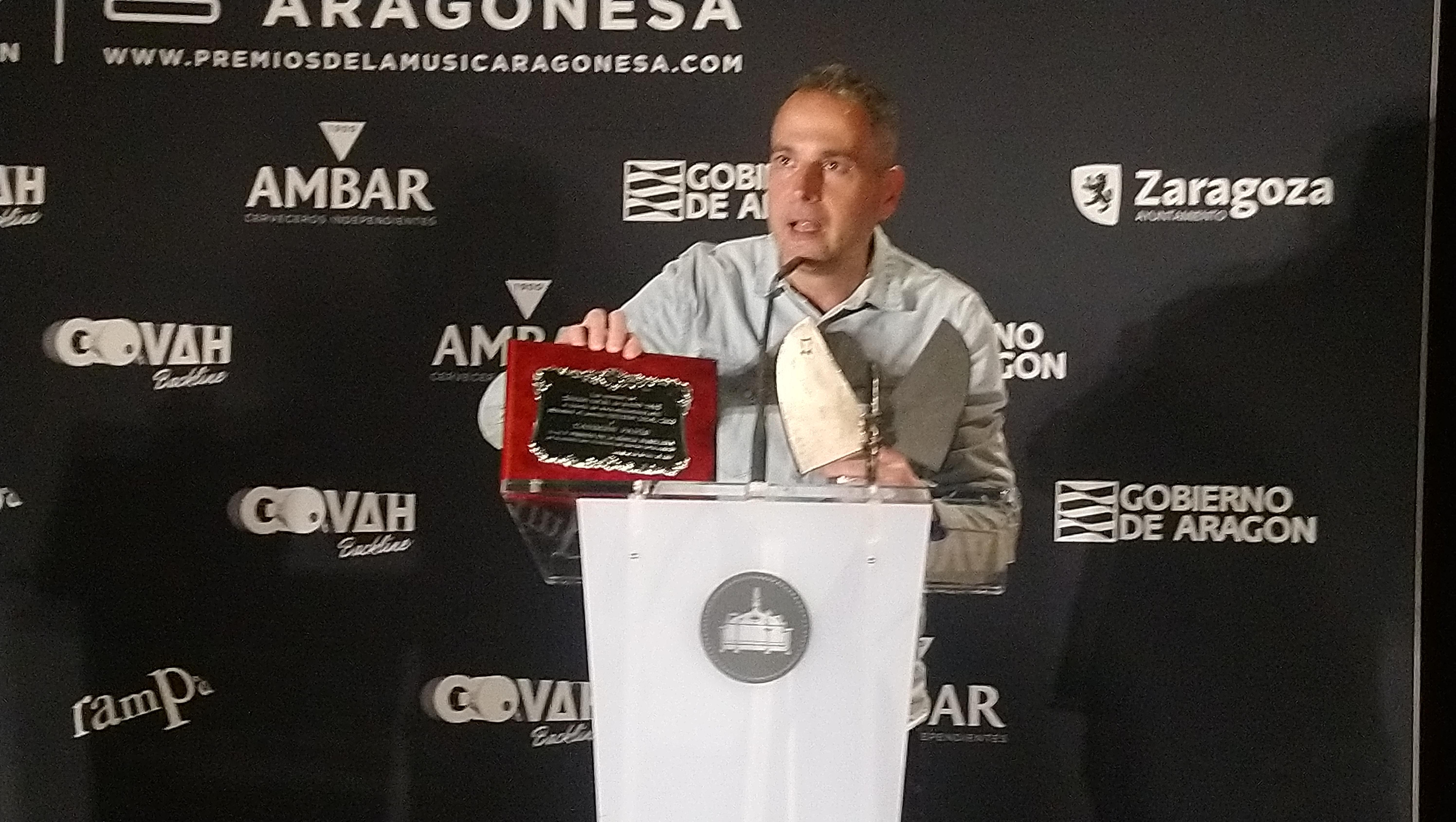 XX Premios de la Música Aragonesa. Sergio Falces, coordinador de Aragón Musical, ostrando cómo era el trofeo de hace 20 años y el actual.